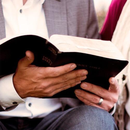 Primer plano de un hombre sosteniendo una Biblia abierta