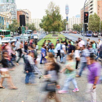 People walking across a street in the city.