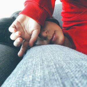 A girl laying her head on the arm of a couch and her hand over her eyes.
