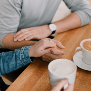 A couple sitting at a table with coffee holding hands.