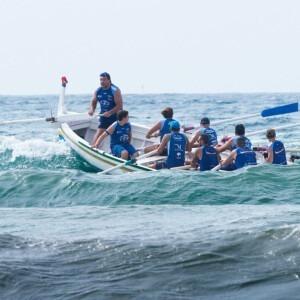 Equipo de remo en barco en alta oleaje.