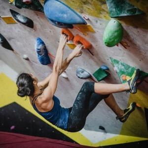 Una mujer fuerte trepando por un muro.