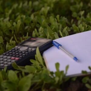 Foto de una calculadora con un bolígrafo y un diario de Ashraf Ali en Unsplash