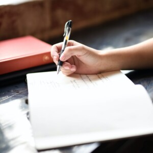Foto de una mano escribiendo en un diario por Hannah Olinger en Unsplash
