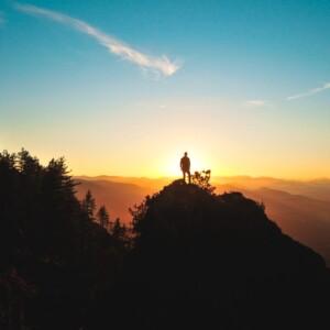 Foto de un hombre en la montaña frente al atardecer por Julentto Photography en Unsplash