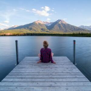 Foto de una niña sentada en un muelle por Kalen Emsley en Unsplash