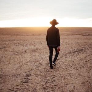 Foto de un hombre caminando en un campo con la Biblia en la mano por Priscilla Du Preez en Unsplash
