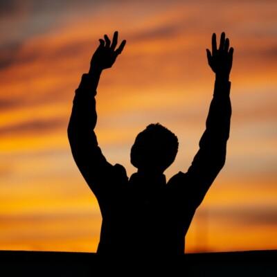 Foto de un hombre levantando los brazos al atardecer por Raphael Nast en Unsplash