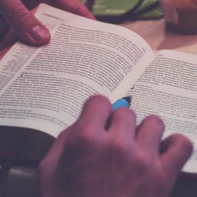 Foto de una Biblia abierta con bolígrafo de mano de Rod Long en Unsplash