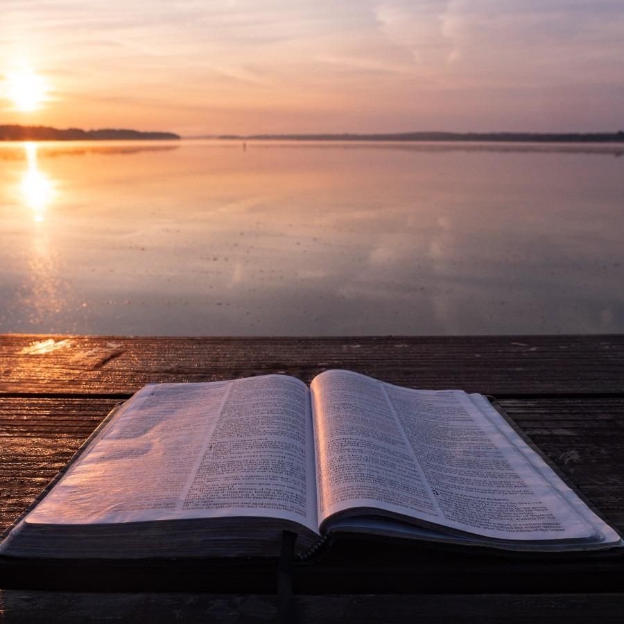 an open Bible on a pier at sunset