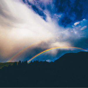 two rainbows in a blue and white sky over a hill with trees