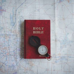 A red Bible on a map with a compass on top