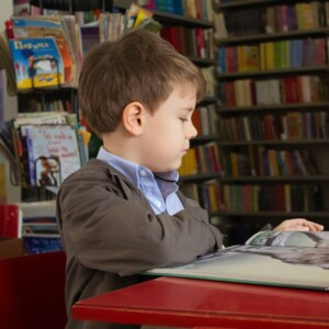little boy sitting in a library and looking at a book