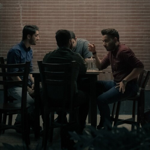 men sitting at a table talking