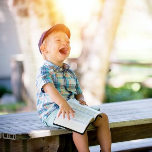boy laughing with Bible on his lap