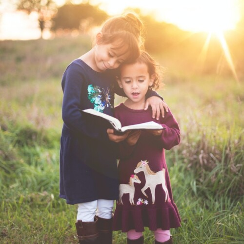two young girls reading the Bible