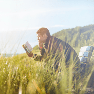 A man sitting on a bench surrounded by tall grass intently reading the Bible with a hand on his chin.