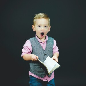 little boy with a surprised face and holding an open Bible