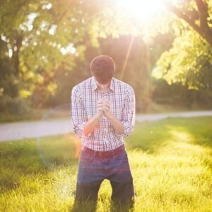 man kneeling in prayer with sunlight shining on him