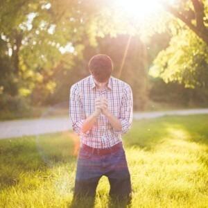 man kneeling in prayer with sunlight shining on him