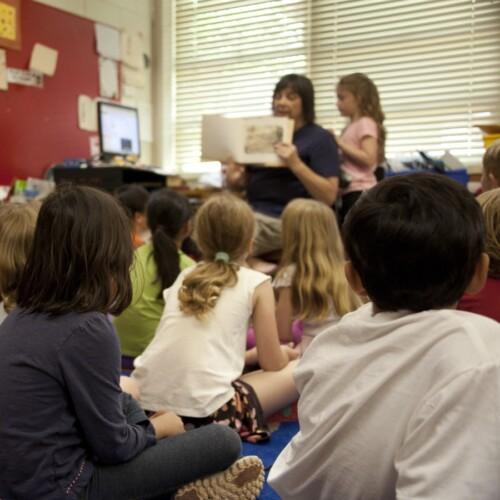 children sitting on floor listening to a teacher