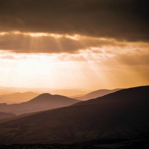 sun rays shining on hills