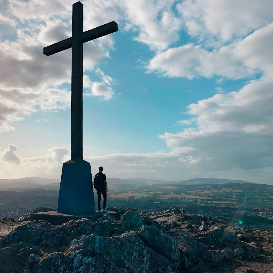 man on mountain with a large cross