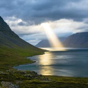 sunlight shining through clouds onto water between hills
