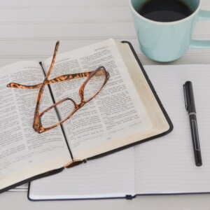 open Bible with glasses, a journal with a pen, and a cup of coffee