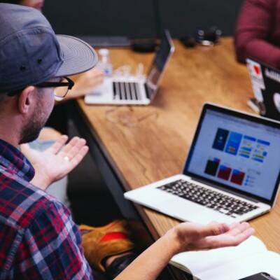 Foto de hombres en una reunión sentados a una mesa con computadoras portátiles por Headway en Unsplash