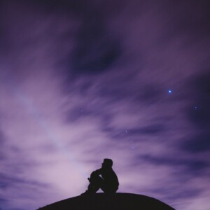 silhouette of man sitting on a hill looking at a night sky