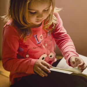 little girl turning the pages of a book