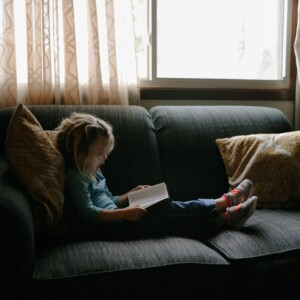 a little girl sitting on a couch, reading a Bible