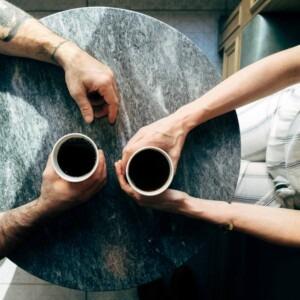 Foto de un hombre y una mujer sentados a la mesa con café por Joshua Ness en Unsplash