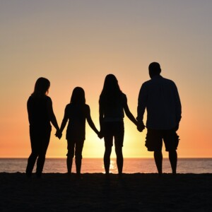 a silhouette of a family at sunset