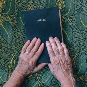 elderly hands on a Bible