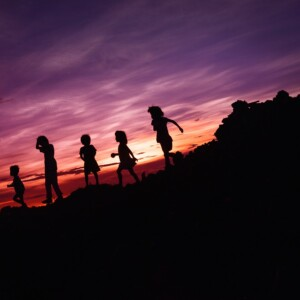 silhouettes of children playing at sunset