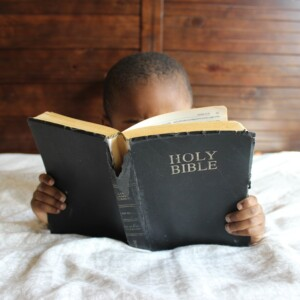 little boy laying down and reading a Bible