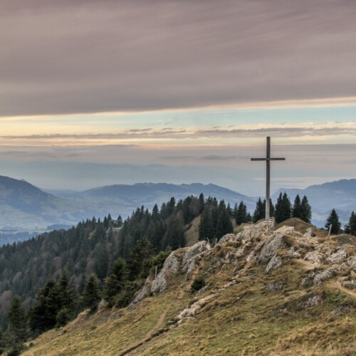 cross on a hill overlooking mountains and trees