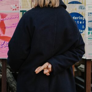 a girl wearing a black coat with fingers crossed behind her back