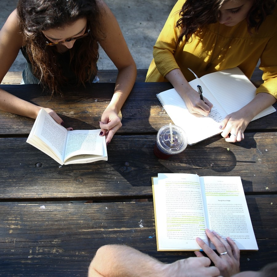 Girls sitting at a picnic table reading and writing.