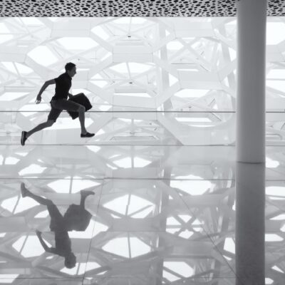 A black and white photo of a man running with a briefcase.