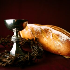 A crown of thorns around a goblet and a loaf of bread.