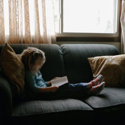 A little girl sitting on a couch reading a Bible.
