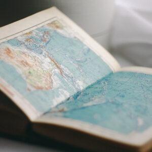 Libro abierto a una imagen de mapa del mundo.