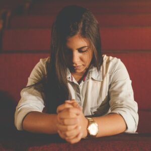 A woman sitting alone in a pew praying.