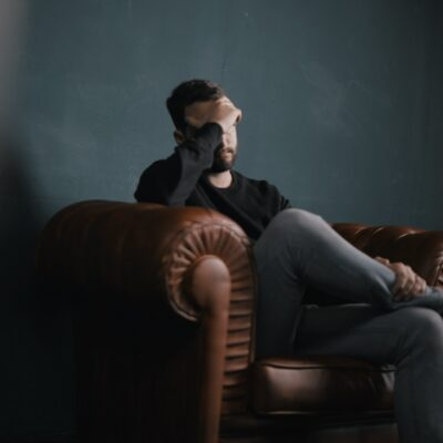 A man sitting on a couch holding his forehead in frustration.