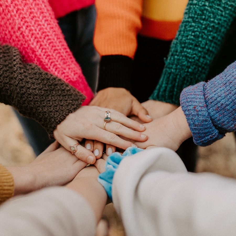 People standing in a circle with hands on top of each other in the middle.