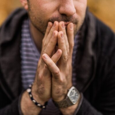A man with his hands together under his chin.
