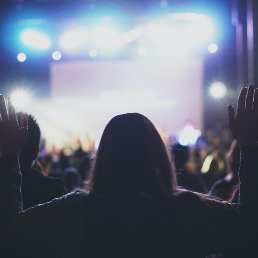 A woman standing in a crowd at church and raising her hands on worship.